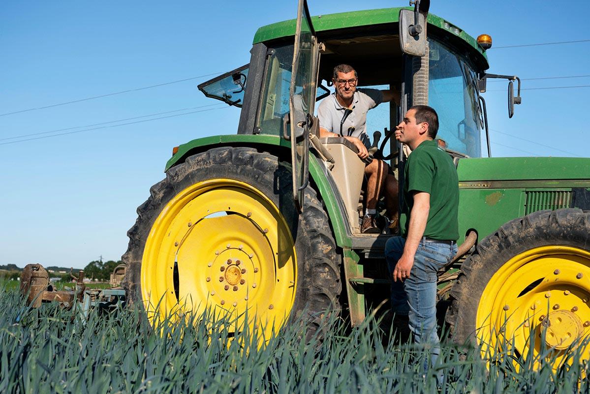 Bertrand discutant avec Louis, au volant de son tracteur, dans leur champs de poireaux primeur