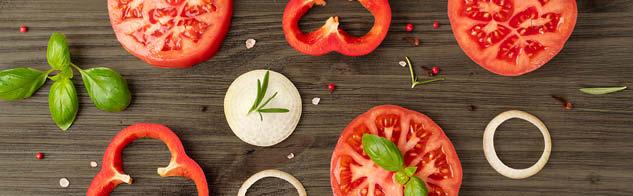 Tomates anciennes et poivrons rouges coupés en tranche et vus du dessus, avec oignons, basilic, romarin et baies